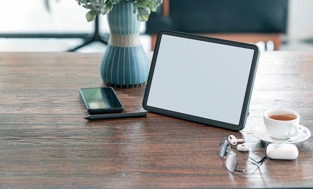 카피 공간이 있는 카페 룸의 나무 테이블에 빈 스크린 태블릿, 가제트, 커피 컵.