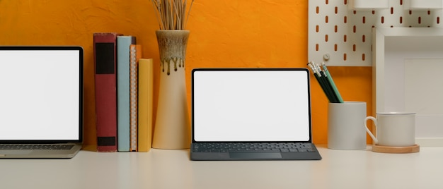 Blank screen tablet and laptop on creative home office desk with books, stationery and decorations