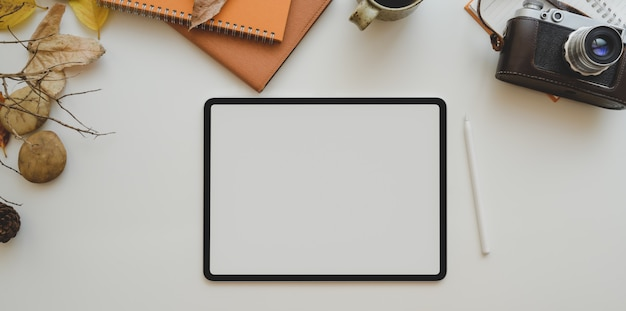 Blank screen tablet and office supplies on white table with copy space