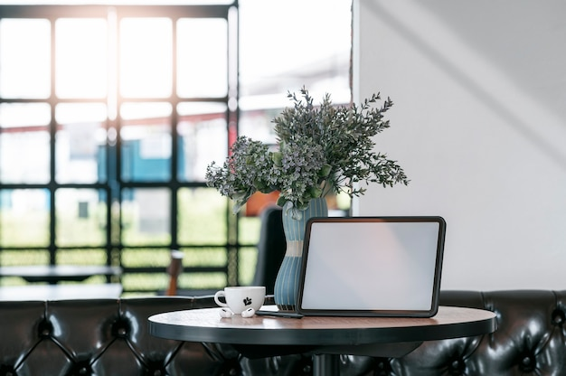 카피 공간이 있는 카페의 둥근 나무 테이블에 빈 스크린 태블릿.