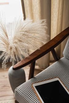 パンパスグラスの花束とレトロな椅子の上の空白の画面のタブレットパッド。ホームオフィスデスクワークスペース