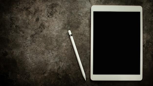 Ручка планшета с пустым экраном и обучение словам на деревянном кубическом блоке на фоне черного стола