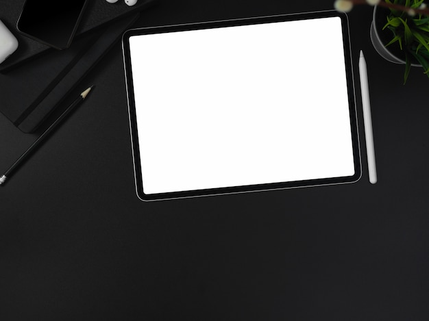 Blank screen tablet, stationery, supplies, decoration and copy space on dark modern worktable