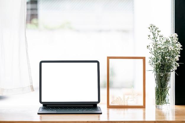 Таблетка пустого экрана с волшебной клавиатурой и деревянной рамкой на столе счетчика.
