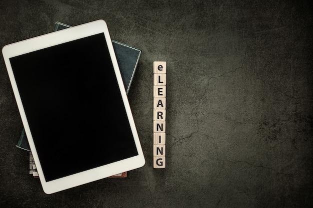 Пустой экран планшета с ноутбуком и электронным обучением на деревянном кубическом блоке на фоне черного стола