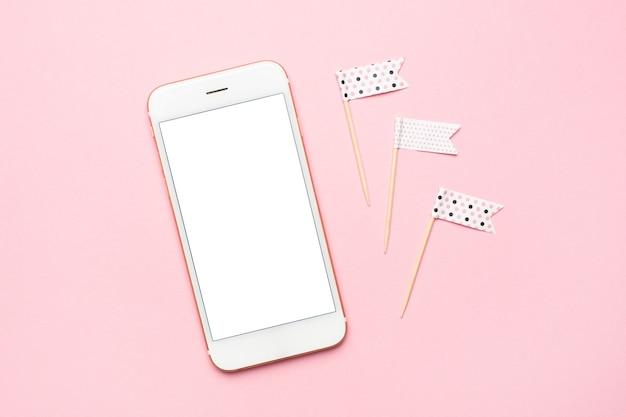 Пустой экран белый мобильный телефон на пастельно-розовом