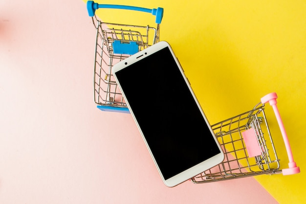 Blank screen white cellphone and shopping carts on pastel pink and yellow background. minimal style, flatlay