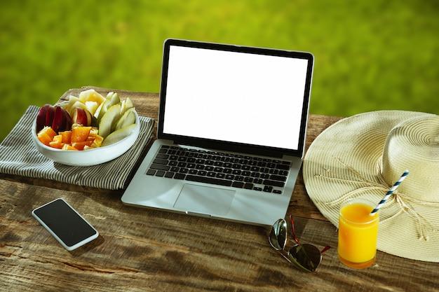 壁に自然と屋外の木製テーブルにノートパソコンとスマートフォンの空白の画面フルーツとフレッシュジュースが近くにあります。創造的な職場、ビジネス、フリーランスの概念。コピースペース。
