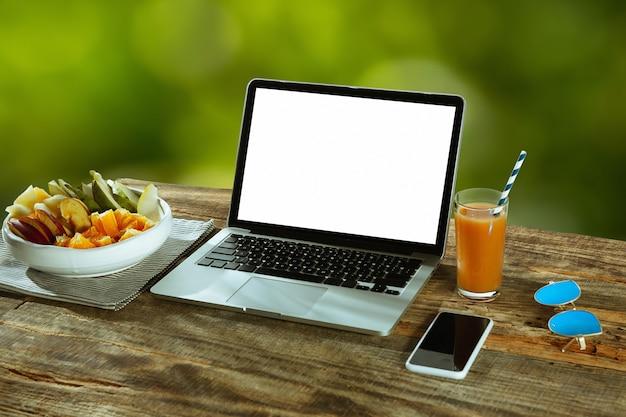 벽에 자연과 야외 나무 테이블에 노트북과 스마트 폰의 빈 화면 과일과 근처 신선한 주스입니다. 창의적인 직장, 비즈니스, 프리랜서의 개념. copyspace.