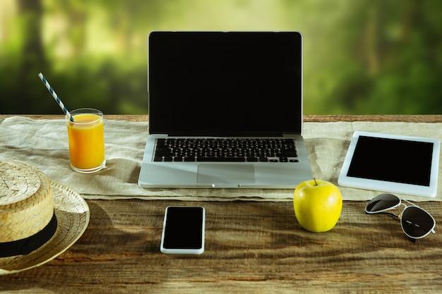 Пустые экраны ноутбука и смартфона на деревянном столе на открытом воздухе с природой на стене фрукты и свежий сок поблизости. концепция творческого рабочего места, бизнеса, фрилансера. copyspace.