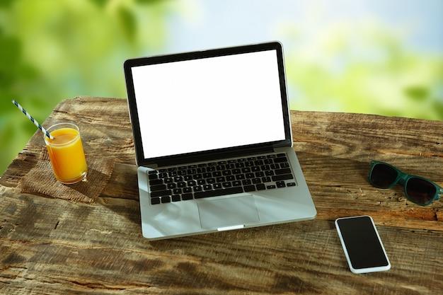 Пустые экраны ноутбука и смартфона на деревянном столе на открытом воздухе с природой на стене, макет.