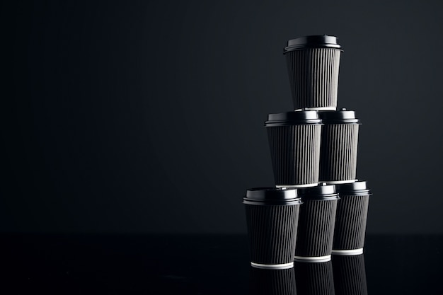 Blank set of black take away cardboard paper cups closed with caps in pyramid shape presented on right side