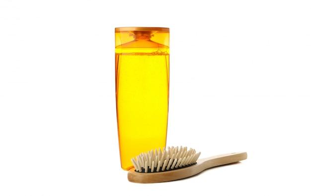 Пустая бутылка шампуня и щетка для волос, изолированные на белом фоне