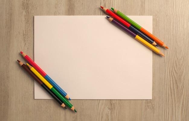 Чистый лист и цветные карандаши на деревянный стол
