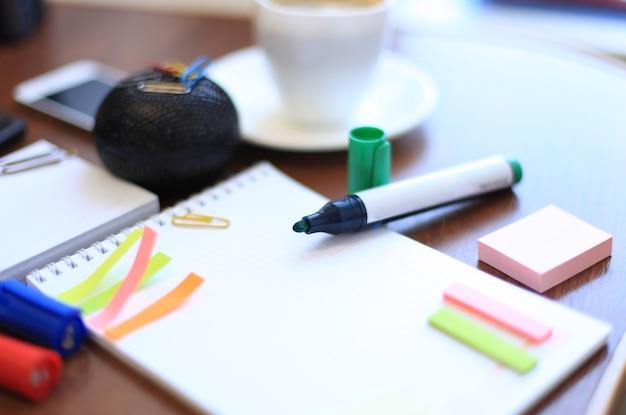 탁자 위에 커피 한 잔이 있는 빈 시트와 문구류