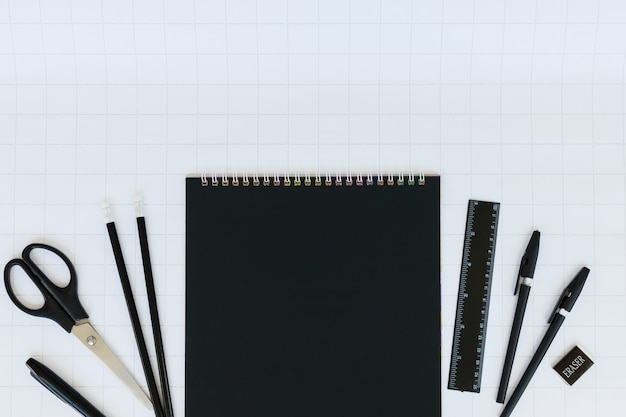 Blank sheet of black notebook paper and stationery set on a white checkered