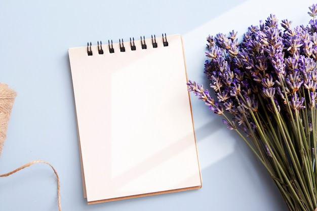 Blank sheet of flat lay notebook with lavender, candle, twine. write your message