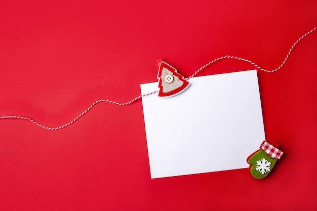Чистый лист для поздравления на красном фоне. рождественская и новогодняя открытка. пустое пространство