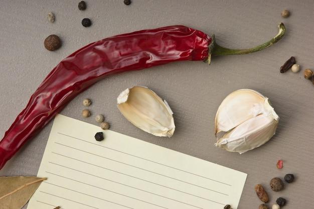 レシピとキッチンテーブルの上のスパイスを調理するための空白のシート