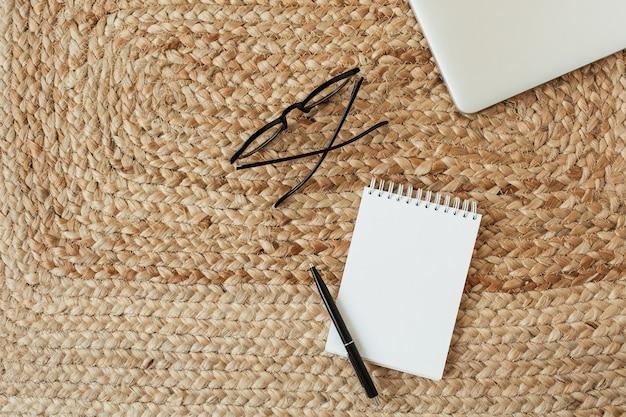 テキスト、メガネ、ペン、籐のわらのラップトップのコピースペースと空白のシートノート