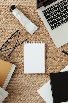 Blank sheet notebook with empty copy space, laptop, glasses. flat lay, top view home office desk table workspace