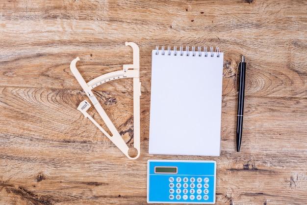 木製のテーブルトップビューレイアウトのメモ帳ペン計算機とキャリパーの空白のシート。適切な栄養、カロリー計算、減量の概念。