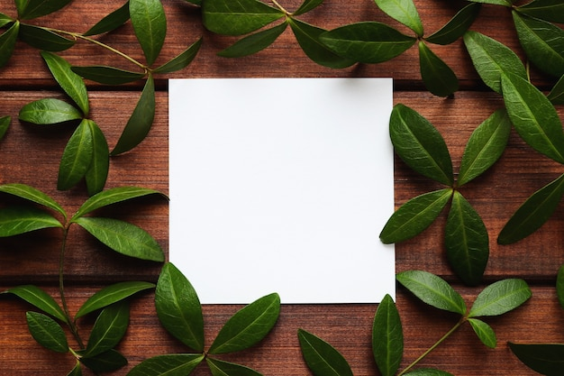 空白の紙と木製の背景の緑の葉のクローズアップデザインまたは招待状のコピースペースのテンプレート Premium写真
