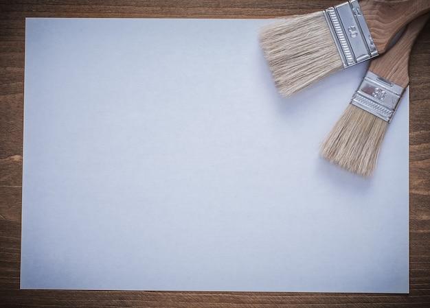紙とペイントブラシの建設コンセプトの空白のシート。