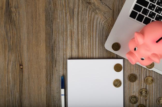 Чистый лист бумаги и розовая копилка рядом с ноутбуком. крупным планом