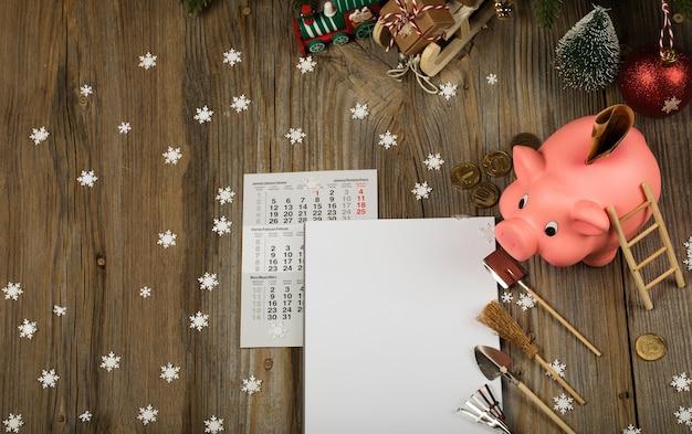 Чистый лист бумаги и розовая копилка на новогоднем фоне новогодние резолюции