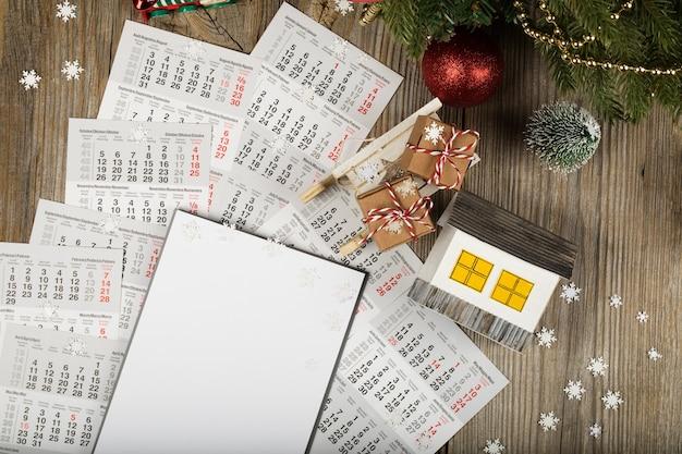 Чистый лист бумаги и небольшой бумажный домик с монетами на новогоднем фоне вид сверху