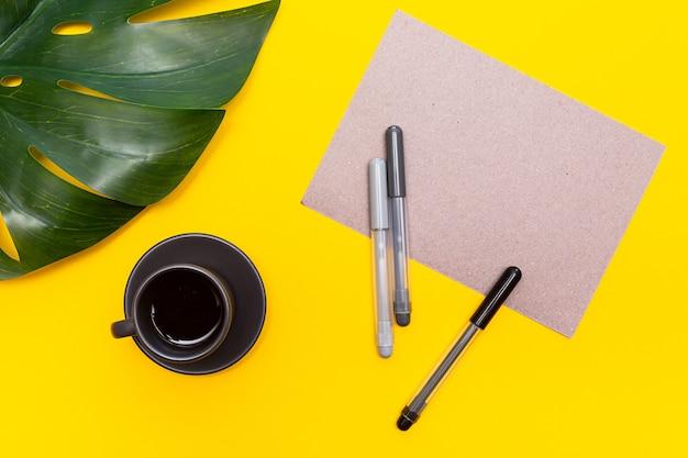 빈 종이, 펠트 펜, 몬스 테라 잎 및 노란색에 블랙 커피 한잔