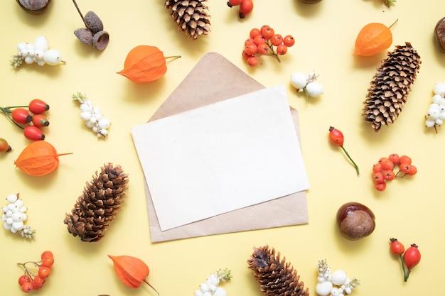 Чистый лист бумаги для текста и осеннего макета с физалисом, шишками, листьями, рябиной