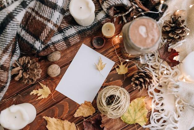 Чистый лист бумаги на деревянном столе сверху. осеннее настроение с листьями, свечами, какао, пледом. вид сверху