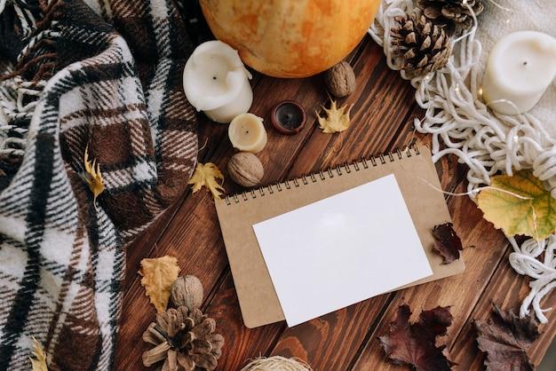 Чистый лист бумаги на деревянном столе сверху. осеннее настроение с листьями, свечами, пледом. вид сверху