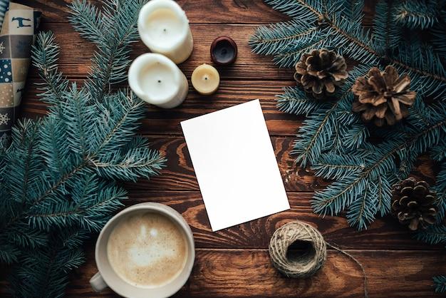クリスマスツリーの枝と一杯のコーヒーと木製のテーブルの上の白紙のシート。上面図