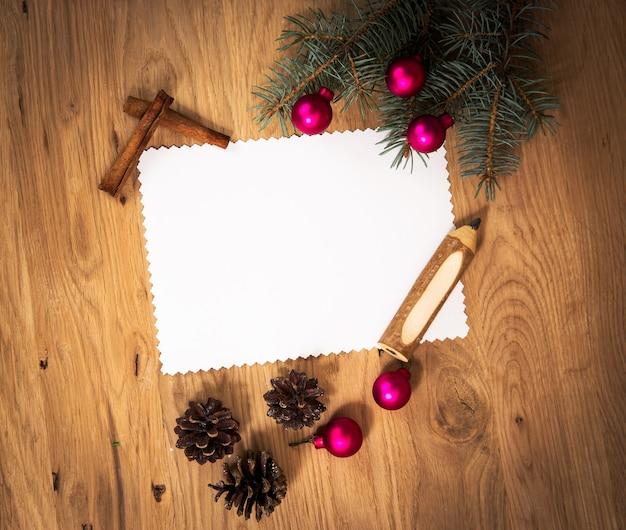 나무 바닥에 연필과 크리스마스 장식이 있는 빈 종이