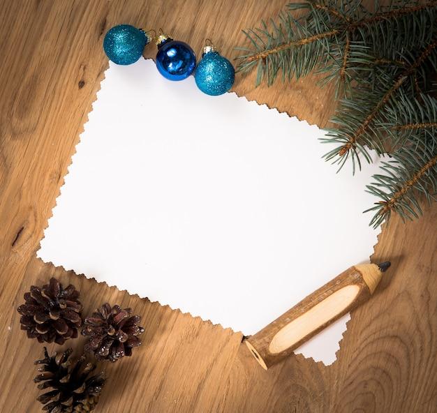 연필과 크리스마스 장식으로 나무 바닥에 종이의 빈 시트
