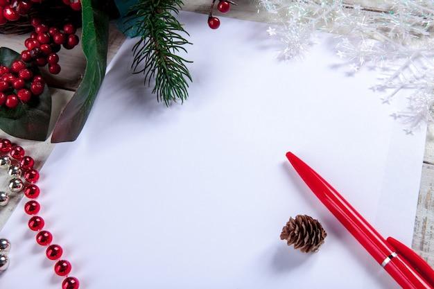 ペンとクリスマスの飾りが付いている木製のテーブルの上の白紙のシート。