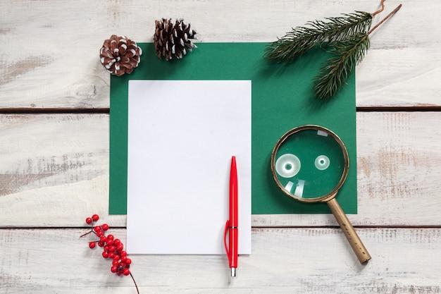 펜 및 크리스마스 장식 나무 테이블에 종이의 빈 시트.