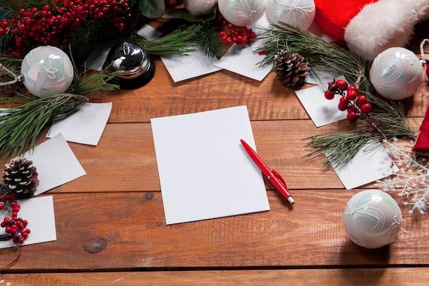 Чистый лист бумаги на деревянном столе с ручкой и рождественскими украшениями.