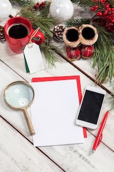 ペン、電話、クリスマスの装飾が施された木製のテーブルの上の白紙。