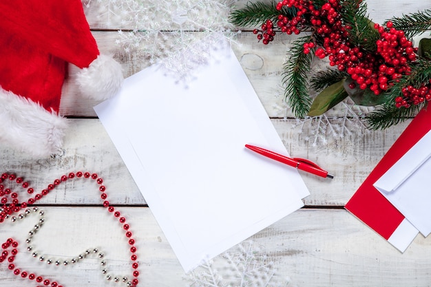 ペンとクリスマスの装飾が付いている木製のテーブルの上の空白の紙