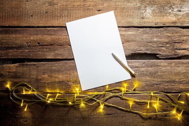 Чистый лист бумаги на деревянном столе с ручкой и рождественскими украшениями