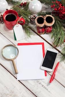 펜, 전화 및 크리스마스 장식 나무 테이블에 종이의 빈 시트