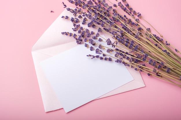 분홍색 배경에 봉투와 라벤더 꽃과 종이의 빈 시트. 간단한 웨딩 카드
