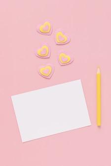 白い紙の白紙、黄色の鉛筆、ピンクの背景にピンクと黄色のハート、幸せなバレンタインデー。テキストの場所。