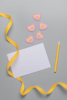 白い紙、黄色いリボン、黄色の鉛筆、灰色の背景にピンクと黄色のハート、ハッピーバレンタインデーの空白のシート。テキストの場所。