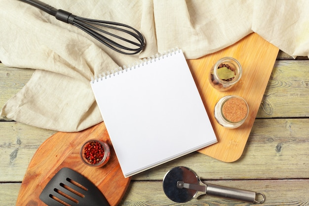 Blank sheet of opened notepad and kitchen utensils on  table with tablecloth, copy space
