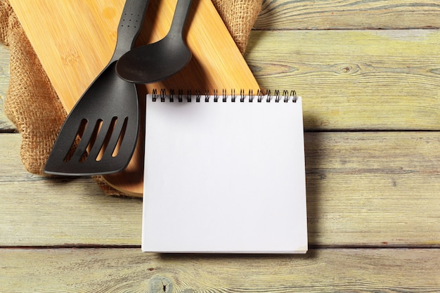 Blank sheet of opened notepad and kitchen utensils on table with tablecloth,